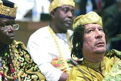 Muammar al-Gaddafi at an African Union meeting, flanked by traditional leaders.