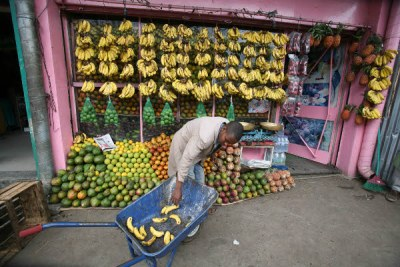 A fruit vendor preparing his stall in Merkato market, Addis Ababa.