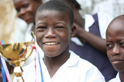 A Liberian student holds a trophy the school won in a government-sponsored spelling bee.