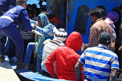 Coastguards help a woman off a boat arriving in Lampedusa from Libya (file photo).