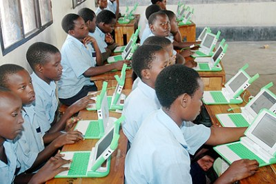 Primary school children using laptops. Over 200,000 units will have been distributed by the end of the year.