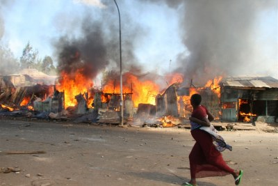 A pregnant woman runs past burning shacks in Nairobi's Mathare slum during 2007 post-election violence (file photo).