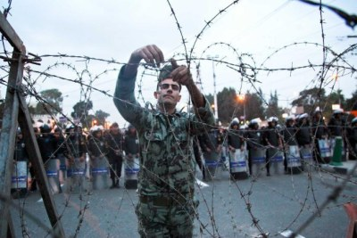 An Egyptian soldier sets up a wire fence in front of the presidential palace.
