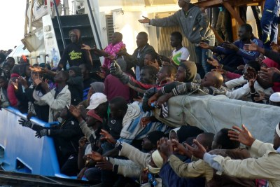 Over 400 migrants intercepted by the Misrata Coast Guard in four inflatable boats in April 2016 reach out for bottles of water being thrown from the shore. Many were later transferred to the Krareem Detention Centre.