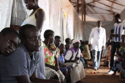 Two South Sudanese teenagers wait in queue to see a doctor at Bidi Bidi Refugee Camp.