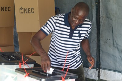 A voter casts his ballot in the first round.