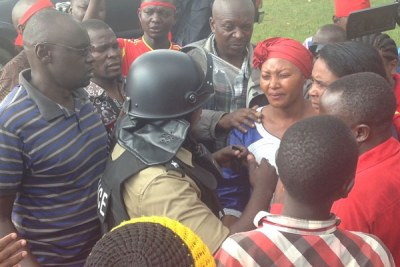 Winfred Kiiza, the leader of the opposition in parliament, centre,  struggles to control tears as she engages a police officer in Mbale after police officers fired teargas to disperse an age limit rally.