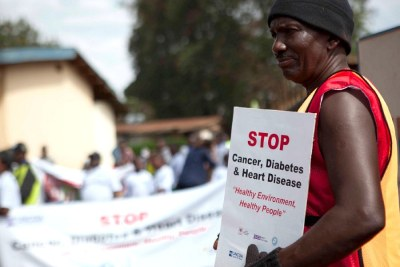 Mike of the Uganda NCDs Alliance leads a parade around the community in Kampala to raise awareness of NCDs.