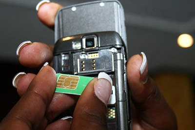 A mobile phone user inserts a SIM card into a phone. (file photo).