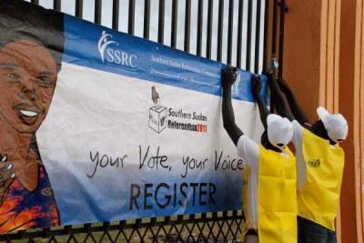 Des Officiels de la commission référendaire du sud Soudan accrochent des posters  àJuba pour inciter à se faire enregistrer sur les listes