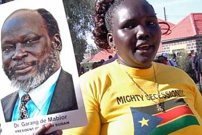 une femme montrant un poster de John Garang