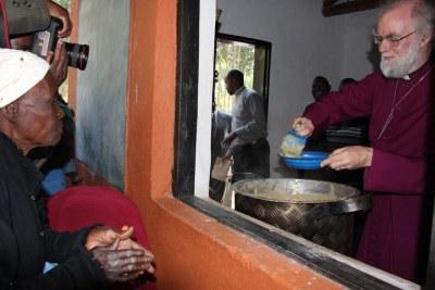 L'Archevêque de Canterbury, Rowan Williams sert le repas lors de sa tournée en Afrique Centrale
