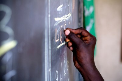 A student writes on a blackboard.