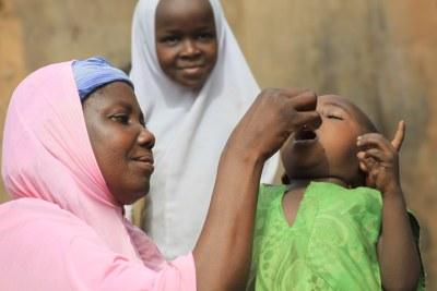 Inna Kanda administers an oral Polio vaccine in Sokoto, northern Nigeria.