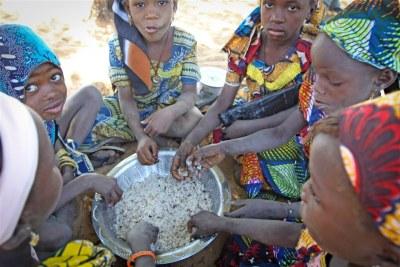 Jeunes filles partageant le repas du midi à un centre d'alimentation scolaire du PAM à Bouza au Niger.