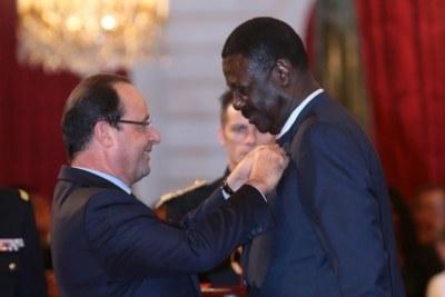 Pape Diouf recevant la Légion d'honneur des mains du président français, François Hollande (09/10/2013)