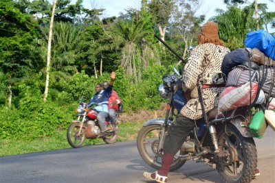 Passers-by on a motorcycle wave to 'dozos' posted along the road between Man and Duékoué in western Côte d'Ivoire.