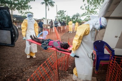 Medical staff bring in a weak patient who had been in contact with people infected with Ebola (file photo).