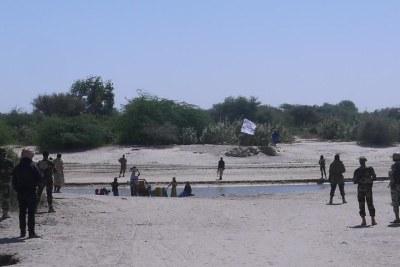 Les soldats nigériens face à des combattants armés de Boko Haram. Au loin, un drapeau des jihadistes.