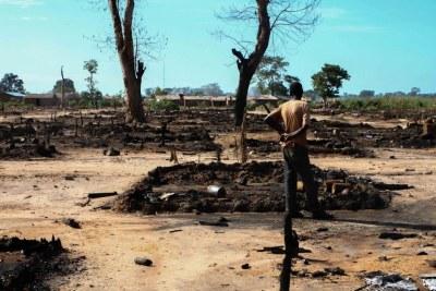 Un homme inspecte sa cabane incendiée le 12 octobre 2016 au camp de déplacés de l'Évêché, République centrafricaine. Les forces de la Séléka ont brûlé au moins 435 huttes dans le camp.