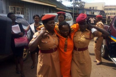 Stella Nyanzi arrives at court supported by prison warders. She told court she was not feeling well.