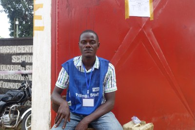 A worker of the National Elections Commission sits at the entrance of a polling precinct.