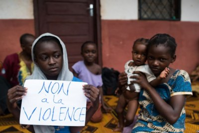 "A young displaced Muslim girl holds a sign saying ""No to Violence"""