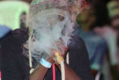 A reveller smokes shisha at a bar in Kisii town on December 25, 2017.
