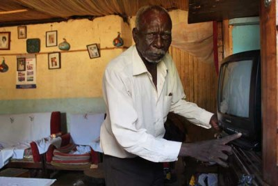 Mzee Benjamin Nyangasi switches off his TV set which can no longer receive any signal after the government shut down analogue broadcasts.