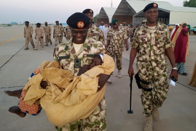 One of the released Dapchi school girls is carried as military and government officials supervise the airlift of the rescued girls at Maiduguri Airport, Nigeria.