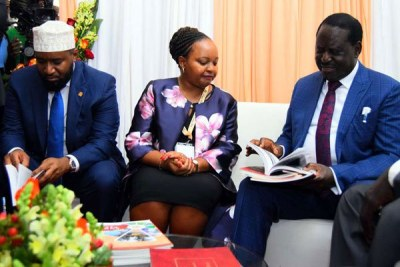 Opposition leader Raila Odinga (right) leafs through a book in the company of Kirinyaga Governor Anne Waiguru and Mombasa Governor Hassan Joho during the devolution conference (file photo).