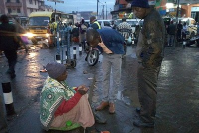 A beggar pleads with city askaris during the dawn operation on May 17, 2018.