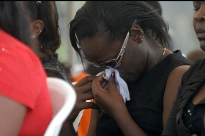 A woman cries out in sorrow during a memorial Mass at Kyadondo Rugby grounds in Kampala on Jul 11, 2011 (file photo).