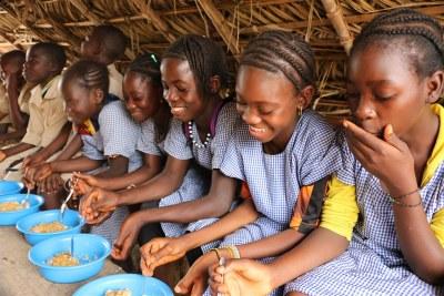 Petites écolières d'un village guinéen à l'heure du repas.