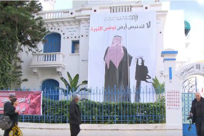 Video screenshot of a poster hung on the office building of the Tunisian Journalists' Syndicate depicting Saudi Prince Mohammed bin Salman holding a chainsaw with the phrase 'no to the desecration of Tunisia, land of the revolution'.