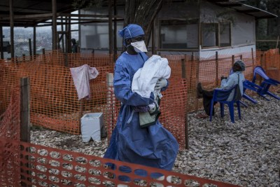 A caretaker already cured from Ebola is seen carrying a four day old baby suspected of having ebola, into a MSF supported Ebola Treatment Centre(ETC)  in Butembo.