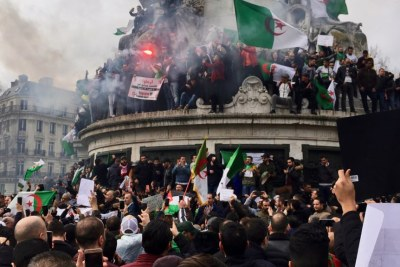 Algerians climbed on the iconic Marianne statue in downtown Paris as the protest against Bouteflika's intention to seeka another term in office.