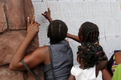(archives) Vérification des noms par des électeurs devant un bureau de vote