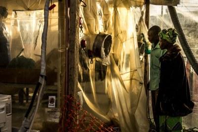 Des parents rendent visite à leur fille de 15 ans, soupçonnée d'être infectée par Ebola, au centre de traitement Ebola à Beni, en RDC (janvier 2019).