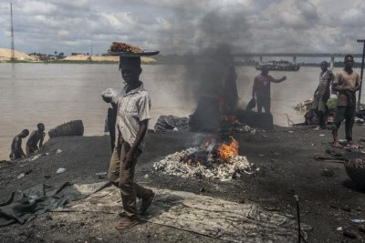 Children in Yenagoa, Bayelsa State, Nigeria pass in front of a flame fed by waste and rubber materials in order to make Kanda, a type of smoked meat, at an abattoir on October 24, 2016. The workers at the slaughterhouse use cow bones, rubber tyres, electric wires, aluminum cans and other waste to sustain the flames, making the fumes very dangerous to inhale.