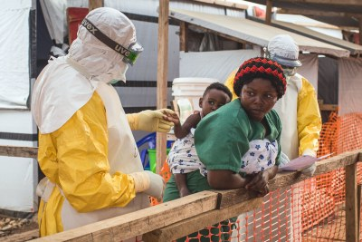 A health worker checks a child potentially infected with Ebola being carried on the back of a caregiver at the Ebola Treatment Centre of Beni, North-Kivu province, Democratic Republic of Congo in March 2019.