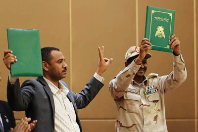 FCC leader Ahmed Rabee and Lt Gen Mohamed Hamdan 'Hemeti' hold copies of the Constitutional Declaration during the signing ceremony in Khartoum.