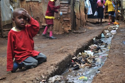 A young boy sits over an open sewer (file photo).