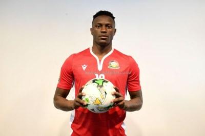 Harambee Skipper Victor Wanyama models the red home jersey.