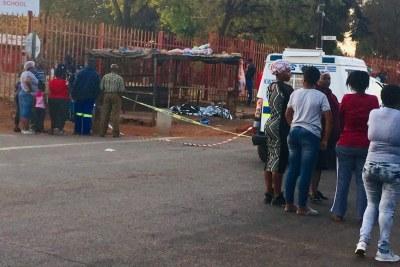 Un homme gît mort sous une bâche en argent dans la section de la ville blanche du canton de Kwathema.