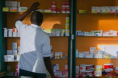 A pharmacist searches for medication on the shelf in Kigali.