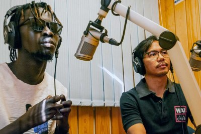 On Radio Miraya's early morning show in South Sudan, Afro-Beat artist Check-B Magic, left, and a representative of the civil society organization War Child Holland discuss his song COVID/Corona, which raises awareness about the novel coronavirus.