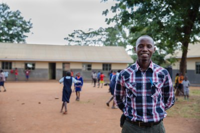 Joseph Munyambanza stands in front of COBURWAS Primary School run by CIYOTA in the heart of Kyangwali Refugee Settlement.