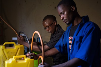 Arthur Woniala (right) of Khainza Energy, aims to package biogas in ten locations near the families, schools and farms that will use it by training 500 small-scale entrepreneurs to produce it around Uganda.