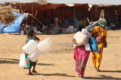Recently arrived refugees from Tigray in Ethiopia bring supplies to help set up their shelter in Raquba camp, in Kassala, Sudan (file photo).